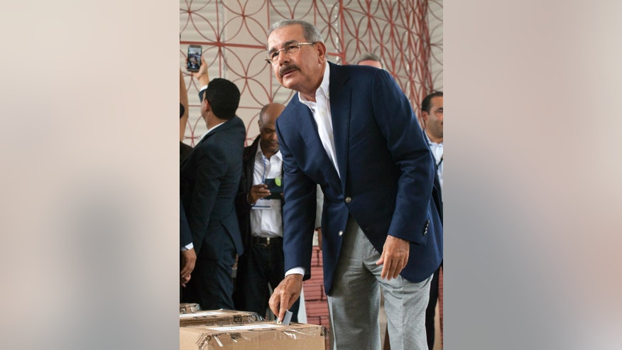 FILE - In this May 15, 2016 file photo, President Danilo Medina casts his ballot during the general elections in Santo Domingo, Dominican Republic. Medina has been sworn in for a second term as leader of the country boasting the best economic grown in Latin America and the Caribbean. Medina was inaugurated Tuesday, Aug. 16, 2016, after winning the highest percentage of the vote in the country's democratic history earlier this year. (AP Photo/Tatiana Fernandez, File)