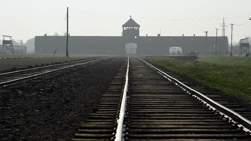 "FILE- In this July 29, 2016, file photo, the entrance to the former Nazi German death camp of Birkenau is lit by the morning sun, in Oswiecim, Poland. The Polish government has approved a new bill that foresees prison terms of up to three years for anyone who uses phrases like ""Polish death camps"" to refer to Auschwitz and other camps that Nazi Germany operated in occupied Poland during World War II. The Justice Ministry said the Cabinet of Prime Minister Beata Szydlo approved the legislation Tuesday, Aug. 16, 2016. (AP Photo/Alik Keplicz, File)"