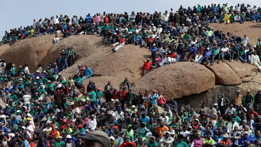 Mine workers sit on a hill during the commemoration near Marikana in Rustenburg, South Africa, Tuesday, Aug. 16, 2016. On August 16, 2012 police shot and killed 34 striking Lonmin miners, apparently while trying to disperse them and end their strike. Ten people, including two police officers and two Lonmin security guards, were killed in the preceding week. (AP Photo/Themba Hadebe)
