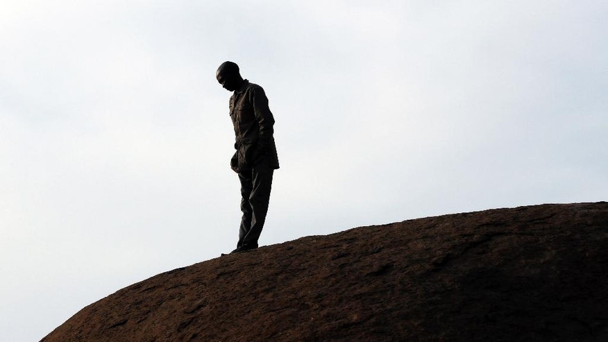 A mine worker stands on a hill waiting for the commemoration to get under way in Marikana in Rustenburg, South Africa, Tuesday, Aug. 16, 2016. On Aug. 16, 2012 police shot and killed 34 striking Lonmin miners, apparently while trying to disperse them and end their strike. Ten people, including two police officers and two Lonmin security guards, were killed in the preceding week. (AP Photo/Themba Hadebe)