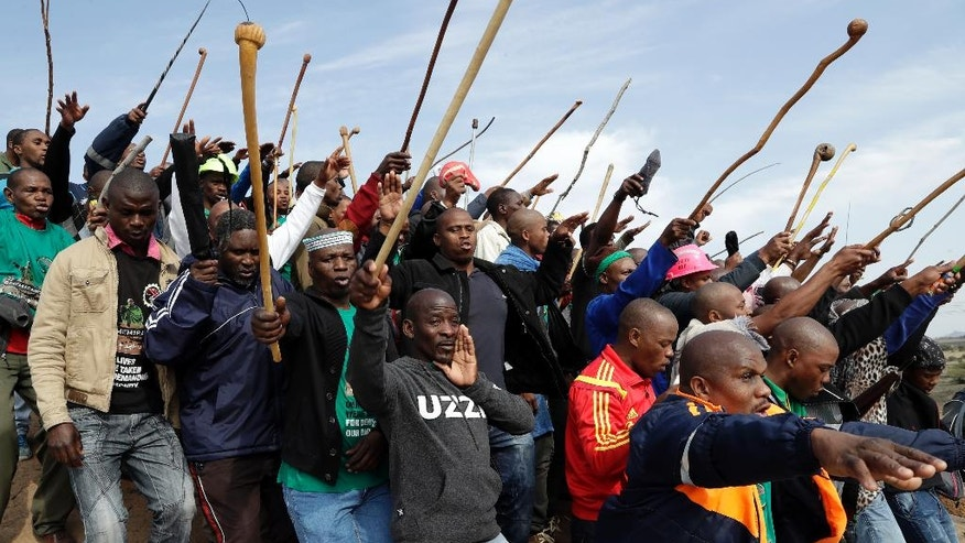 Mine workers sing as they wait for the commemoration to get under way near Marikana in Rustenburg, South Africa, Tuesday, Aug. 16, 2016. On August 16, 2012 police shot and killed 34 Lonmin striking miners, apparently while trying to disperse them and end their strike. Ten people, including two police officers and two Lonmin security guards, were killed in the preceding week. (AP Photo/Themba Hadebe)