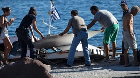 A Coast guard officer and two men move on the dock parts of a tourist vessel in Aegina, southwest of Athens, Tuesday, Aug. 16, 2016. A speedboat collided with a tourist vessel off the Greek island of Aegina near Athens, killing four people, including a child, and injuring at least another four, the coast guard said. (Yannis Liakos/InTime News via AP)