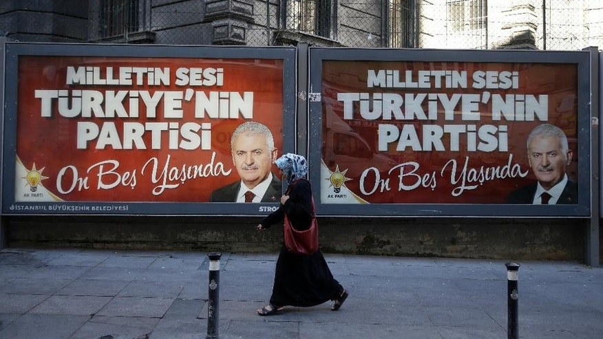 A woman passes a picture of the Turkish Prime Minister Binali Yildirim for the 15th anniversary of AKP party as the sign reads ''The people's voice, Turkey's party, it's now fifteen years old'' in Istanbul, Monday, Aug. 15, 2016. Turkey's state-run news agency says police teams are conducting operations at three Istanbul courthouses as part of an investigation into the July 15 abortive coup. (AP Photo/Thanassis Stavrakis)