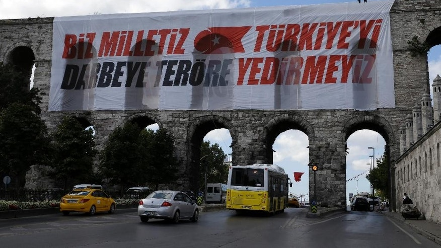 Vehicles pass the Valens Aqueduct with a banner reading ''We are the nation, we won't let Turkey fall to coups and terrorism'' in Istanbul, on Monday, Aug. 15, 2016. Turkey's state-run news agency says police teams are conducting operations at three Istanbul courthouses as part of an investigation into the July 15 abortive coup. (AP Photo/Thanassis Stavrakis)