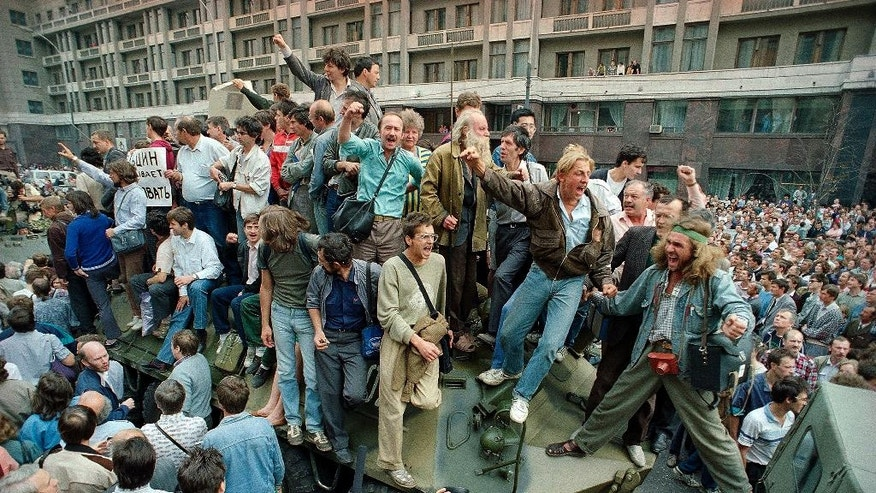 FILE - In this Aug. 19, 1991 file photo, crowds of people surround and climb on tanks which were stopped by the crowd as they drove towards the Red Square area of Moscow, Russia, during a military coup after the announced ousting of Mikhail Gorbachev from power. As the 25th anniversary of the so-called August Coup draws near this Friday, The Associated Press has talked to participants and witnesses of those critical days when Muscovites turned out to defend the spirit of democracy that Gorbachev had unleashed, and many Soviet officers defied their orders and sided with the people, ensuring that that the plotters failed.  (AP Photo/Boris Yurchenko, file)