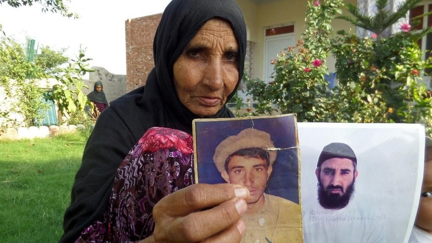 "In this Tuesday, Aug. 16, 2016, photo, the mother of Obiadullah, holds pictures of her son, who was recently released from the Guantanamo Bay detention center, at her home in the village of Haiderkhil, Mandozai district of Khost province, Afghanistan. Obiadullah's family said they're excited their son is among 15 prisoners released from Guantanamo and transferred to the United Arab Emirates this week. They say Obiadullah is now ""free"" after 14 years in the U.S. prison in Cuba and that they can hardly wait to hear from him. (AP Photo/Nishanuddin Khan)"