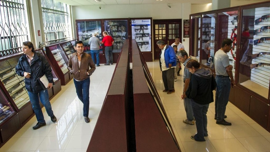 In this July 15, 2016 photo, customers look over guns available for purchase at the country's lone gun store in Mexico City. The store sold 549 guns in 2000. For 2015, sales rose to 10,115 guns, an increase reflecting the rise in concern about personal safety. (AP Photo/Nick Wagner)
