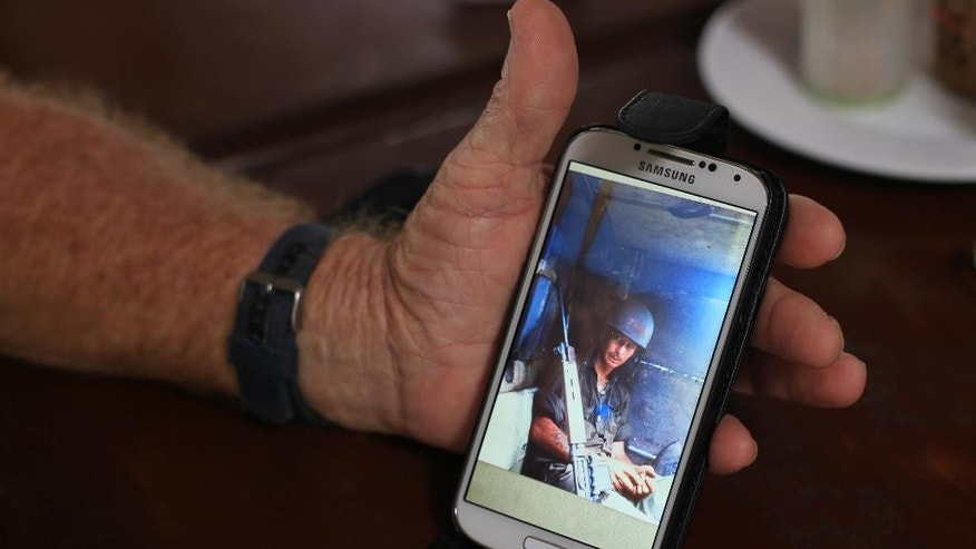 Australian veteran Jeffrey Morris shows a photo of himself taken when he served in Long Tan during the Vietnam war in Vung Tau city, Vietnam on Wednesday, Aug 17, 2016. Australia is making top-level appeals to Vietnam on Wednesday to lift a sudden ban on veterans commemorating the 50th anniversary of Australia's most costly battle of the Vietnam War.(AP Photo/Hau Dinh)