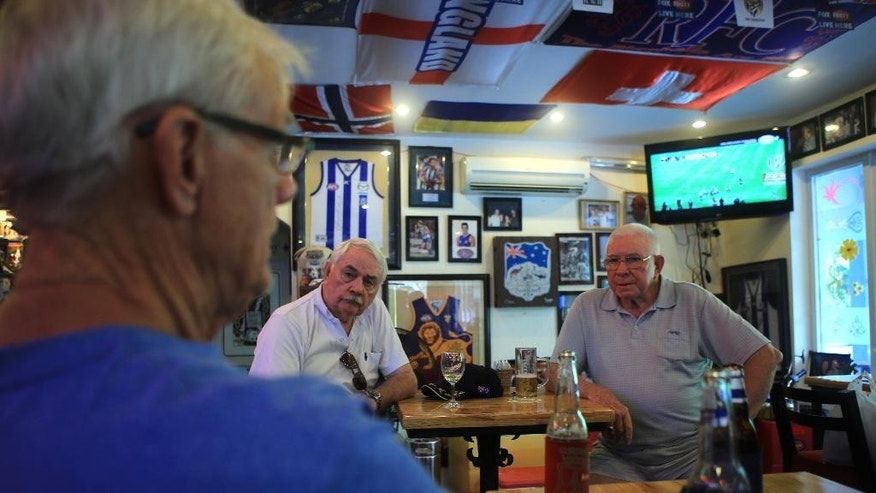 Australian veteran Ernie Gimm, right, talks with friends at a bar in Vung Tau city, Vietnam on Wednesday, 17 August 2016. Australia is making top-level appeals to Vietnam on Wednesday to lift a sudden ban on veterans commemorating the 50th anniversary of Australia's most costly battle of the Vietnam War.(AP Photo/Hau Dinh)