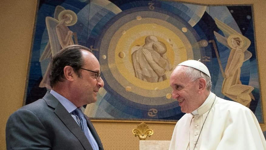 Pope Francis and French President Francois Hollande, left, exchange gifts on the occasion of their private audience at the Vatican, Wednesday, Aug. 17, 2016. Hollande is visiting Pope Francis for a special audience after a spate of Islamic extremist attacks over recent months left more than 200 dead, including an elderly French priest. (L'Osservatore Romano/Pool Photo via AP)