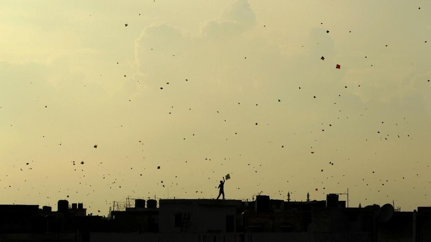 FILE- In this Aug. 15, 2013 file photo, a boy flies a kite from the roof of a house as other kites seem to flock in the sky above as Indians celebrate Independence Day in New Delhi, India. Indian police say three people, including two children, have died after their throats were slashed by glass-coated kite string used in competitions to slice the strings of other kites.The deaths occurred in New Delhi on Monday, which was a holiday on account of India's Independence Day when people fly kites to celebrate. (AP Photo/Tsering Topgyal, File)