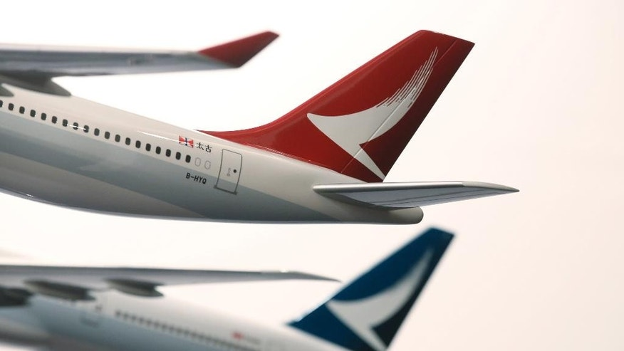 FILE - In this Jan. 28, 2016, file photo, two model jets of Hong Kong airline Cathay Dragon, formerly known as Dragonair, front, and Cathay Pacific Airways, are displayed at a news conference in Hong Kong.  Cathay Pacific Airways says its profit tumbled in the first half of this year as economic weakness in China and other important markets cut passenger demand while it faced cutthroat competition from rivals.  Hong Kong's biggest airline on Wednesday, Aug. 17, 2016,  posted interim net profit of 353 million Hong Kong dollars ($45.5 million), down 82 percent from the same period a year earlier.  (AP Photo/Kin Cheung, File)