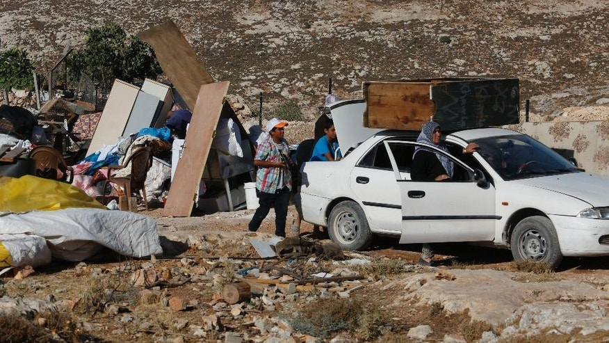 In this Tuesday, August 16, 2016 photo, Palestinians pack their belongings after their family house was demolished by Israeli troops in the West Bank village of Sair, near the town of Hebron. Israel said houses were destroyed because lack of building permit, while Palestinians say permits are virtually impossible to obtain and that Israel is evicting them from their land. (AP Photo/Nasser Shiyoukhi)