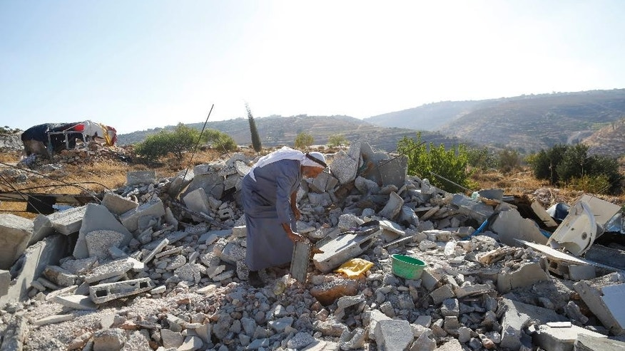 In this Tuesday, August 16, 2016 photo, a Palestinian inspects the rubble of a family house demolished by Israeli troops in the West Bank village of Sair, near the town of Hebron. Israel said houses were destroyed because lack of building permit, while Palestinians say permits are virtually impossible to obtain and that Israel is evicting them from their land. (AP Photo/Nasser Shiyoukhi)