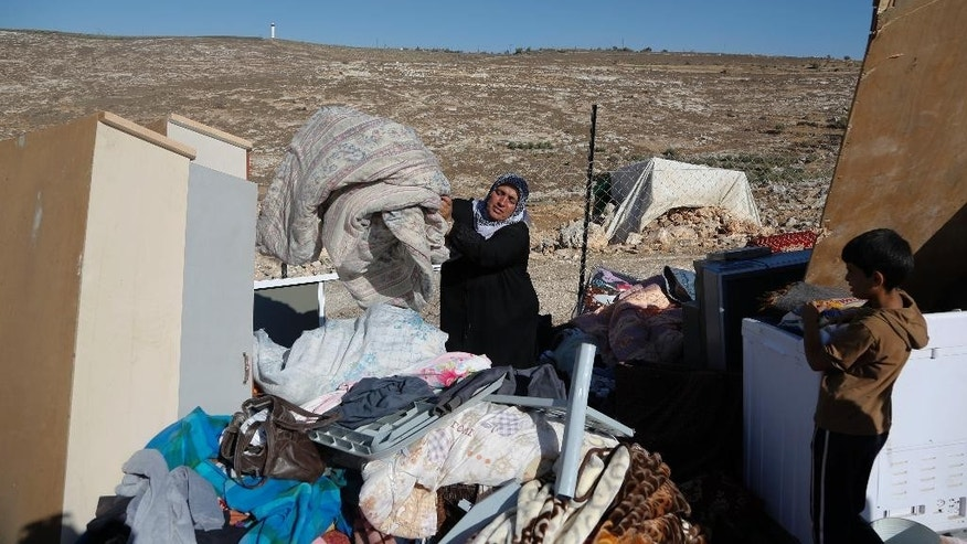 In this Tuesday, August 16, 2016 photo, Palestinian woman goes through her belongings after her family house was demolished by Israeli troops in the West Bank village of Sair, near the town of Hebron. Israel said houses were destroyed because lack of building permit, while Palestinians say permits are virtually impossible to obtain and that Israel is evicting them from their land. (AP Photo/Nasser Shiyoukhi)
