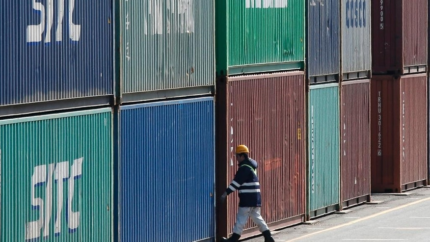 In this Feb. 18, 2016 photo, a port worker walks through the piled containers in Tokyo. Japan posted a trade surplus of 513.5 billion yen ($5.1 billion) in July, though exports sank 14 percent from a year earlier as the yen surged against the dollar, the government reported Thursday, Aug. 18, 2016. (AP Photo/Shuji Kajiyama)