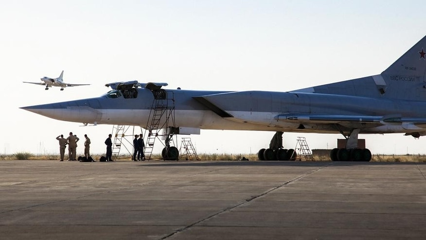 In this photo taken on Monday, Aug. 15, 2016, a Russian Tu-22M3 bomber stands on the tarmac while another plane lands at an air base near Hamedan, Iran.  Russian warplanes took off on Tuesday Aug. 16, from Iran to target Islamic State fighters and other militants in Syria, widening Moscow's bombing campaign in Syria.(WarfareWW Photo via AP)
