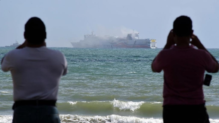 Pedestrians make photos with their smart phones of smoke spilling from the cruise ship Caribbean Fantasy off the coast of San Juan, Puerto Rico, Wednesday, Aug. 17, 2016. Authorities in Puerto Rico say more than 500 passengers have been evacuated after a small fire erupted on a cruise ship that runs between Puerto Rico and the Dominican Republic. (AP Photo/Carlos Giusti)