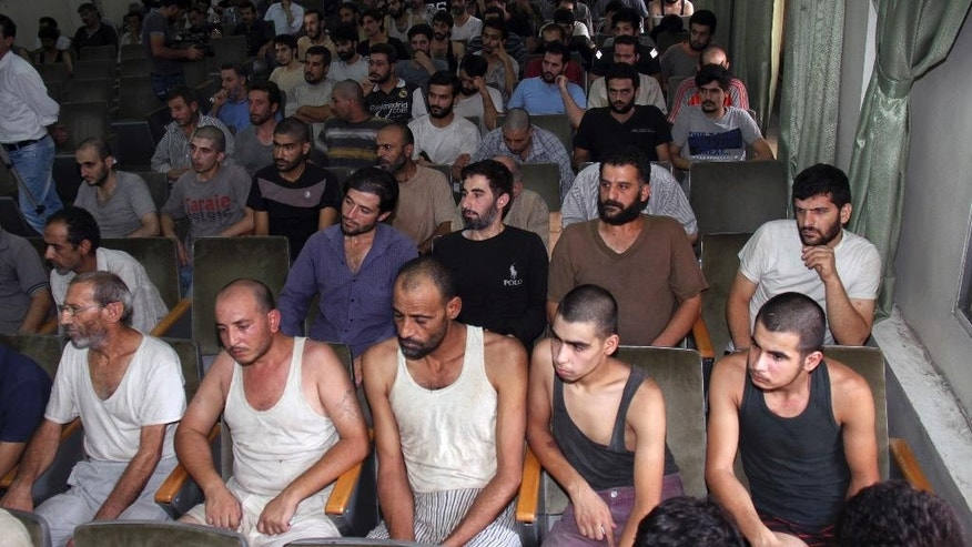 FILE - In this Saturday, Sept. 1, 2012, file photo, Syrian prisoners sit in a courtroom before their release in Damascus, Syria. The Amnesty report highlights new statistics from the Human Rights Data Analysis Group, or HRDAG, an organization that uses scientific approaches to analyze human rights violations, which indicate that 17,723 people died in custody across Syria between March 2011 and the end of 2015. (AP Photo/Bassem Tellawi, File)