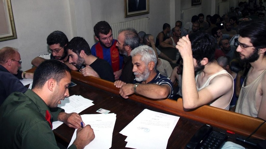 FILE - In this Saturday, Sept. 1, 2012, file photo, Syrian prisoners sign their papers of release at the Damascus Police Command headquarters in Damascus, Syria. The Amnesty report highlights new statistics from the Human Rights Data Analysis Group, or HRDAG, an organization that uses scientific approaches to analyze human rights violations, which indicate that 17,723 people died in custody across Syria between March 2011 and the end of 2015. (AP Photo/Bassem Tellawi, File)