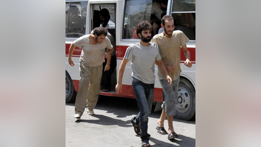 FILE - In this Saturday, Sept. 1, 2012, file photo, Syrian prisoners file out of a bus before their release from custody at the Damascus Police Command headquarters in Damascus, Syria. The Amnesty report highlights new statistics from the Human Rights Data Analysis Group, or HRDAG, an organization that uses scientific approaches to analyze human rights violations, which indicate that 17,723 people died in custody across Syria between March 2011 and the end of 2015. (AP Photo/Bassem Tellawi, File)