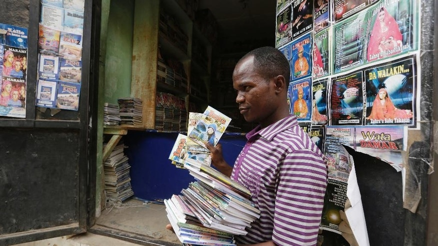 In this photo taken Monday April, 4. 2016, a Book hawker, Adamu Saidu, displays books he purchased at Kurmi Market to be sold in villages inaccessible by car in Kano, Nigeria. In the local market stalls are signs of a feminist revolution with piles of poorly printed books by women, as part of a flourishing literary movement centered in the ancient city of Kano, that advocate against conservative Muslim traditions such as child marriage and quick divorces.  dozens of young women are rebelling through romance novels, many hand-written in the Hausa language, and the romances now run into thousands of titles. (AP Photo/Sunday Alamba)