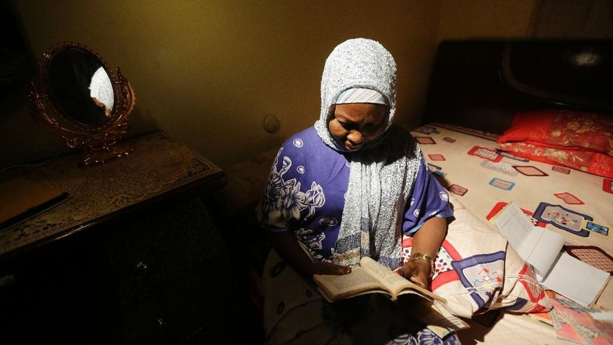 In this photo taken Tuesday April, 5. 2016 author Hadiza Nuhu Gudaji, reads through one of her novels in her bedroom in Kano, Nigeria. In the local market stalls are signs of a feminist revolution with piles of poorly printed books by women, as part of a flourishing literary movement centered in the ancient city of Kano, that advocate against conservative Muslim traditions such as child marriage and quick divorces.  dozens of young women are rebelling through romance novels, many hand-written in the Hausa language, and the romances now run into thousands of titles.  (AP Photo/Sunday Alamba)