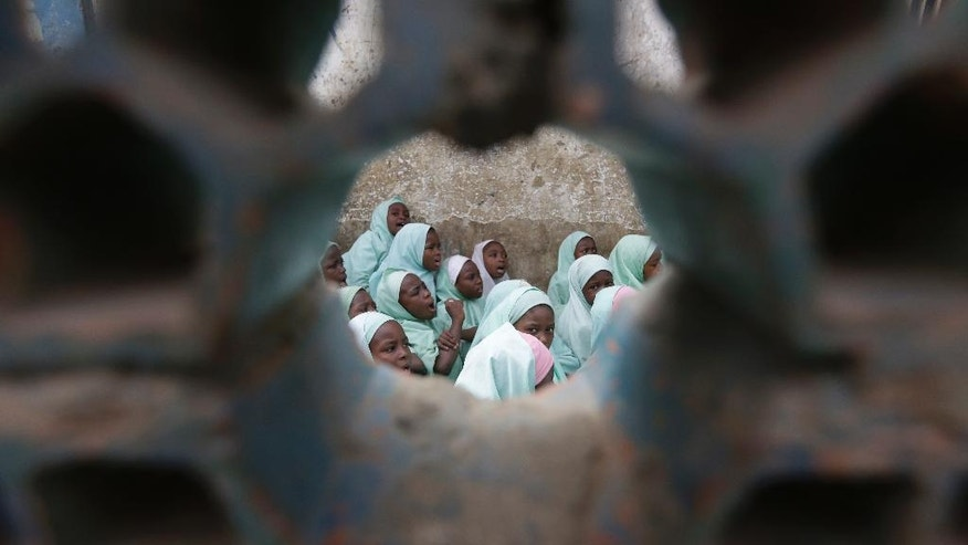 In this photo taken Wednesday April, 6. 2016 , Muslim girls rehearse a Quran in a school in Kano, Nigeria.  In the local market stalls are signs of a feminist revolution with piles of poorly printed books by women, as part of a flourishing literary movement centered in the ancient city of Kano, that advocate against conservative Muslim traditions such as child marriage and quick divorces. (AP Photo/Sunday Alamba)
