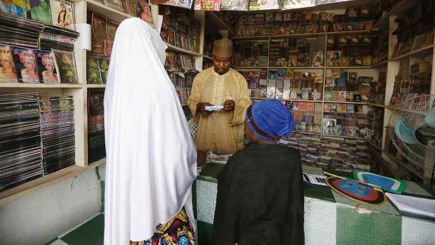 In this photo taken Sunday April, 3. 2016, Suleiman Maharazu, centre, the owner of Maharazu Bookshop, sells books to young girls in his shop in Kano, Nigeria. In the local market stalls are signs of a feminist revolution with piles of poorly printed books by women, as part of a flourishing literary movement centered in the ancient city of Kano, that advocate against conservative Muslim traditions such as child marriage and quick divorces.  dozens of young women are rebelling through romance novels, many hand-written in the Hausa language, and the romances now run into thousands of titles. (AP Photo/Sunday Alamba)