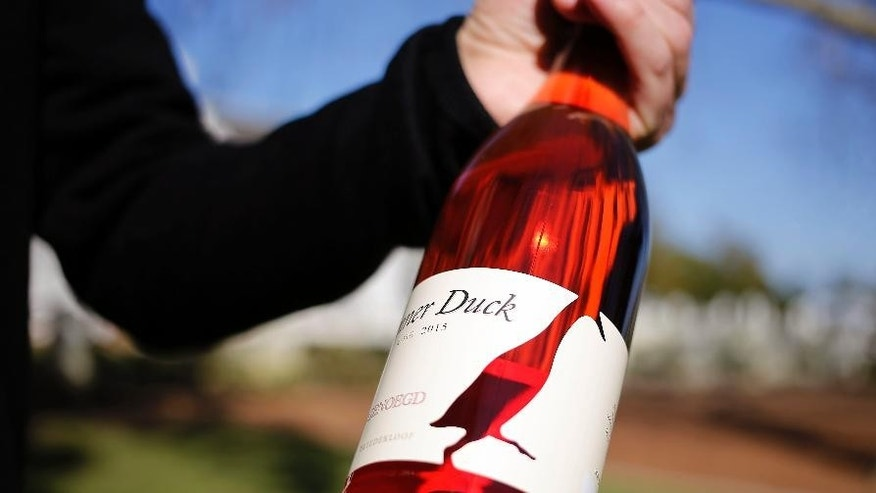 In this photo taken on Wednesday, Aug. 10, 2016, a bottle of wine called the Runner Duck, that is produced on the Vergenoegd wine estate on the outskirts of Stellenbosch, South Africa, This wine farm is winning praise from environmentalists for using Indian runner ducks instead of chemicals to eradicate pests like snails and bugs from its vineyards. (AP Photo/Schalk van Zuydam)