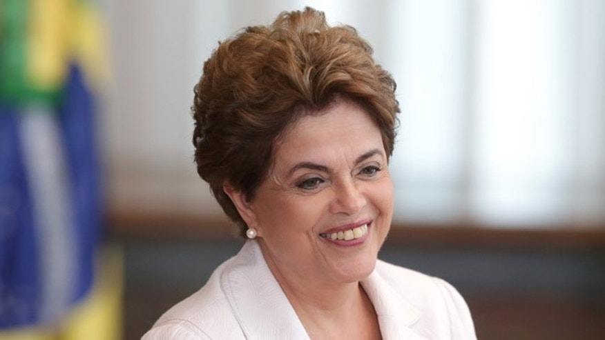 Brazil's suspended President Dilma Rousseff smiles as she arrives to read a letter to the people and to the Senate of Brazil, from Alvorada Palace, in Brasilia, Brazil, Tuesday, Aug. 16, 2016. President Rousseff is proposing to let Brazilians decide if they want to hold new, early presidential elections if lawmakers restore her to power. (AP Photo/Eraldo Peres)
