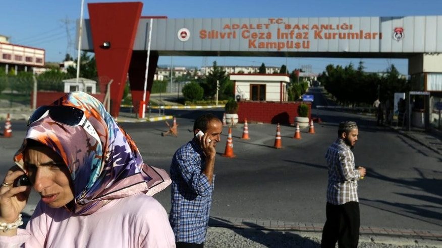 Relatives and friends of prisoners wait outside a high security prison complex in Silivri, about 80 kilometers (50 miles) west of Istanbul, Wednesday, Aug. 17, 2016. Turkey issued a decree Wednesday paving the way for the conditional release of some 38,000 prisoners, the justice minister said, an apparent move to reduce its prison population to make space for thousands of people who have been arrested as part of an investigation into last month's failed coup. (AP Photo/Thanassis Stavrakis)