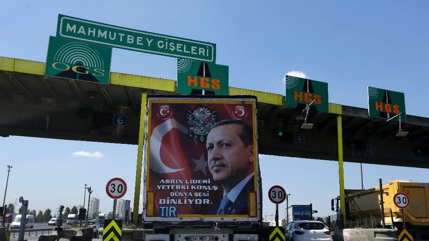 The back of a truck carries a poster portrait of Turkish President Recep Tayyip Erdogan and reading ''The leader of this century may you speak, the whole world listening to you,'' passes the highway toll station in Istanbul, on Wednesday, Aug. 17, 2016. Turkey issued a decree Wednesday for the conditional release of some 38,000 low level prisoners, Justice Minister Bekir Bozdag said Wednesday, in a move being seen as reducing its prison population to make space for thousands of people arrested following last month's failed coup. (AP Photo/Thanassis Stavrakis)