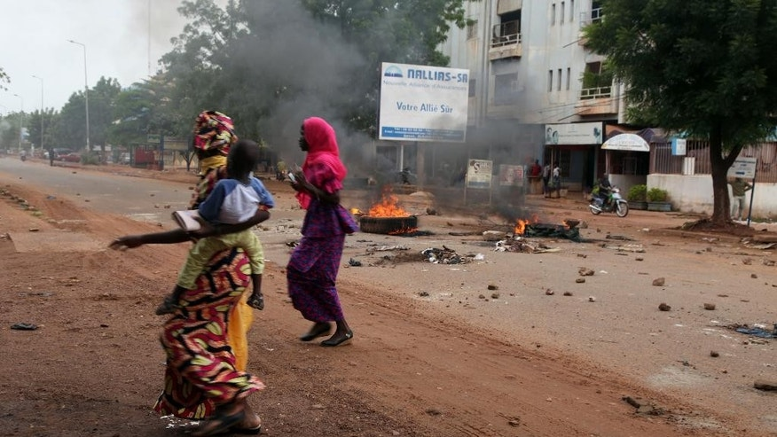 Women and a child past by a burning tyre on a road, after a protest, in Bamako, Mali, Wednesday, Aug. 17, 2016. Protests in Mali's capital against the arrest of a popular activist radio host have turned violent, leaving at least three people dead and several injured. (AP Photo/Baba Ahmed)