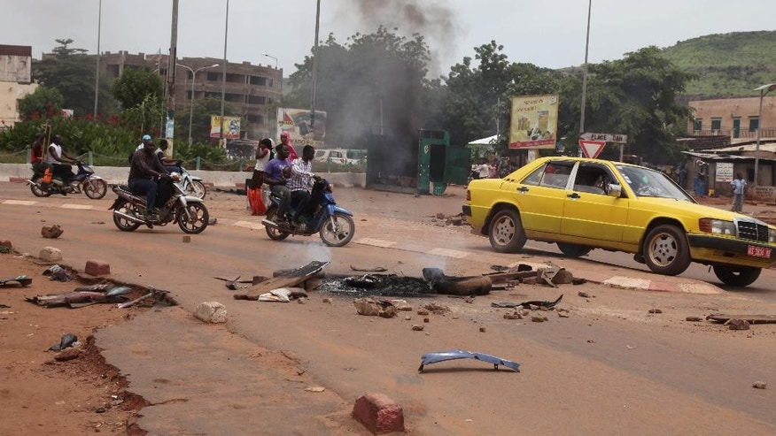 Debris from a burning tyre on a road, after a protest, in Bamako, Mali, Wednesday, Aug. 17, 2016. Protests in Mali's capital against the arrest of a popular activist radio host have turned violent, leaving at least three people dead and several injured. (AP Photo/Baba Ahmed)