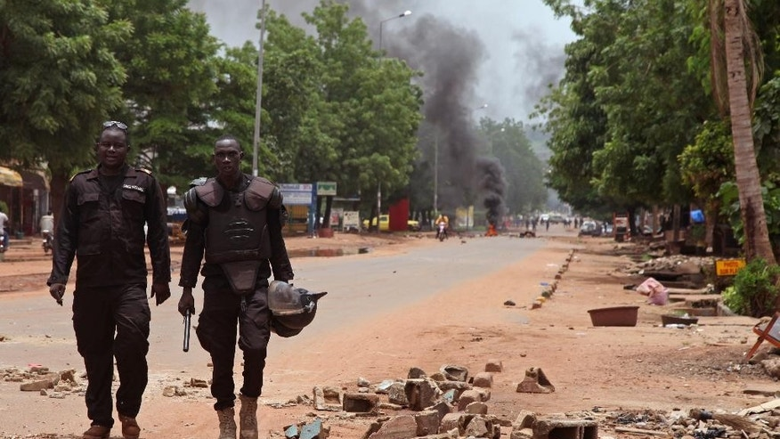 Mali police walk among the debris after a protest, in Bamako, Mali, Wednesday, Aug. 17, 2016. Protests in Mali's capital against the arrest of a popular activist radio host have turned violent, leaving at least three people dead and several injured. (AP Photo/Baba Ahmed)