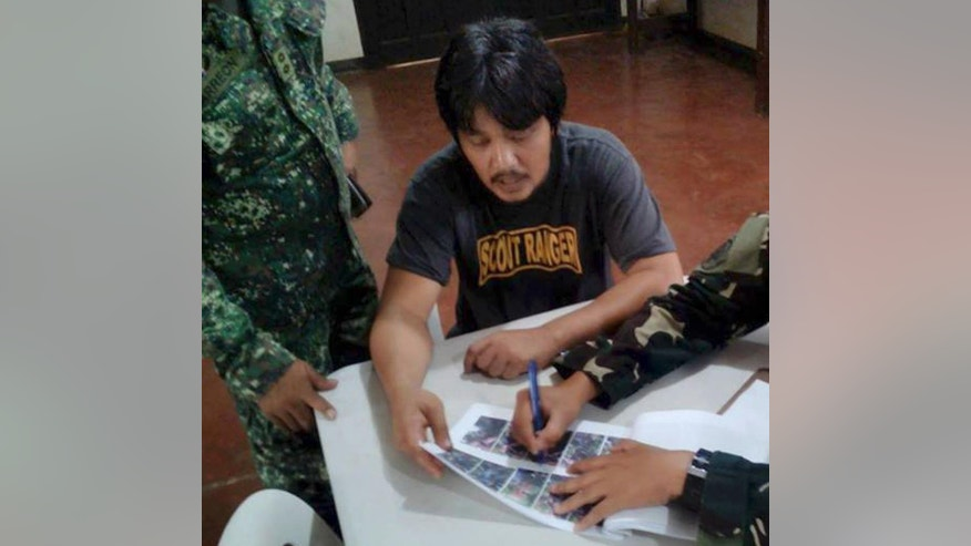 In this photo provided by WESTMINCOM, Chief Officer of the tugboat Charles, Ismail, center, undergoes a debriefing facilitated by the Joint Task Force Sulu, at military headquarters, in Mindanao, southwest Philippines, Thursday, Aug. 18, 2016.. Ismail, whose seven crewmen were abducted near Philippine waters in June, was recovered by troops Wednesday, Aug. 17, 2016,  along a road in southern Jolo Island's Luuk town, said Maj. Filemon Tan, a regional military spokesman. (WESTMINCOM via AP)