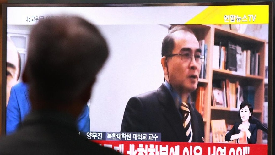 "A man watches a TV news airing a file image of Thae Yong Ho, minister at the North Korean Embassy in London, at Seoul Railway Station in Seoul, South Korea, Wednesday, Aug. 17, 2016. Thae has defected to South Korea, becoming one of the highest Northern officials to do so, South Korea said Wednesday. The letters read ""He was the No. 2 man at the embassy"". (AP Photo/Ahn Young-joon)"