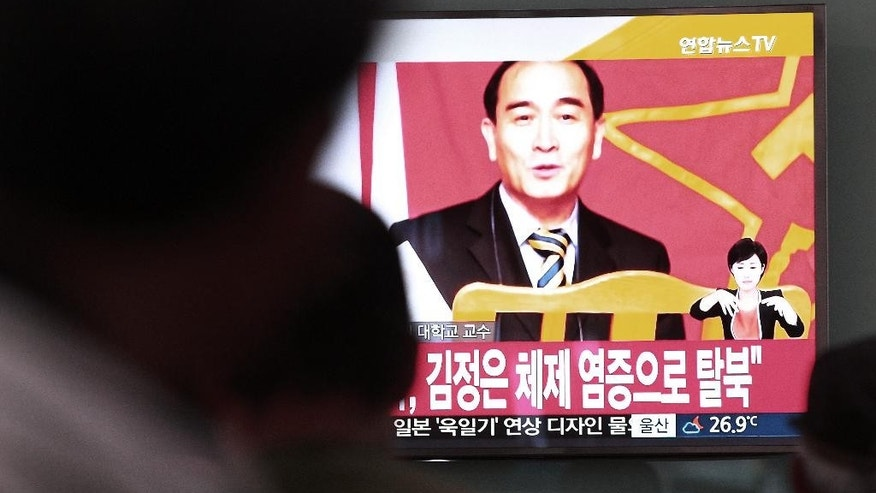 "People watch a TV news showing a file image of Thae Yong Ho, minister at the North Korean Embassy in London, at Seoul Railway Station in Seoul, South Korea, Wednesday, Aug. 17, 2016. Thae has defected to South Korea, becoming one of the highest Northern officials to do so, South Korea said Wednesday. The letters read ""Thae defected due to his disillusionment with the North's regime under Kim Jong Un "". (AP Photo/Ahn Young-joon)"
