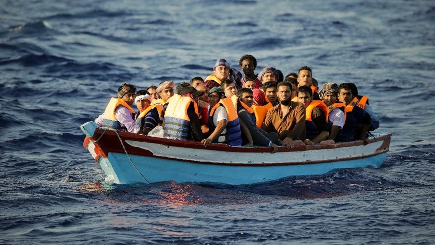 Migrants who are fleeing Libya, crowded onto a dinghy before being helped by members of a Spanish NGO, during a rescue operation at the Mediterranean sea, about 25 miles north of Sabratha, Libya, Thursday, Aug. 18, 2016.  At least three people have died on Thursday morning during the sinking of a wooden boat full with migrants as they tried to reach the Italian coasts. (AP Photo/Emilio Morenatti)