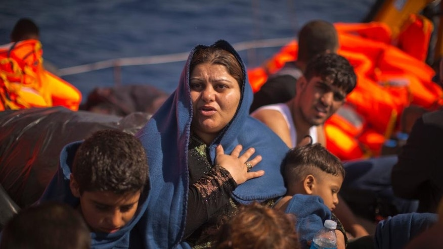 Lebanese Rasmeah sits with her five children aboard a rescue boat assisted during the sinking of their wooden boat by members of a Spanish NGO, during a rescue operation at the Mediterranean sea, about 25 miles north of Sabratha, Libya, Thursday, Aug. 18, 2016. At least three people have died on Thursday morning during the sinking of a wooden boat full with migrants as they tried to reach the Italian coasts. (AP Photo/Emilio Morenatti)