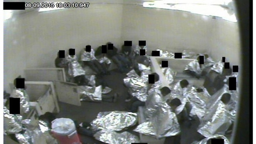 Surveillance camera image of men sitting in a Tucson Border Patrol holding cell wrapped in Mylar sheets. (U.S. Border Patrol)