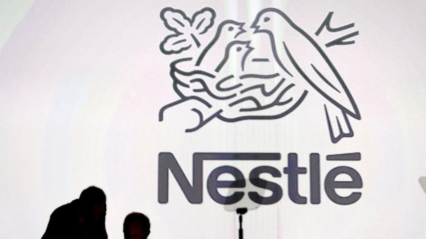 FILE - In this April 7, 2016  file picture  Nestle's directors speak in front of the Nestle's logo during the general meeting of the world's biggest food and beverage company, Nestle Group, in Lausanne, Switzerland. Swiss food and beverage giant Nestle says Thursday Aug. 18, 2016 first-half profits dipped due to a one-time tax expense even as revenues edged up behind growth in its key North American food business and despite a slowdown in the Chinese market. (Laurent Gillieron/Keystone via AP,file)