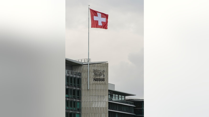 FILE - In this Oct. 15, 2015 file picture tThe Swiss flag flies at  the headquarters building  of the world's biggest food and beverage company, Nestle Group, in Vevey, Switzerland. Swiss food and beverage giant Nestle says Thursday Aug. 18, 2016 first-half profits dipped due to a one-time tax expense even as revenues edged up behind growth in its key North American food business and despite a slowdown in the Chinese market.  (Jean-Christophe Bott/Keystone via AP)