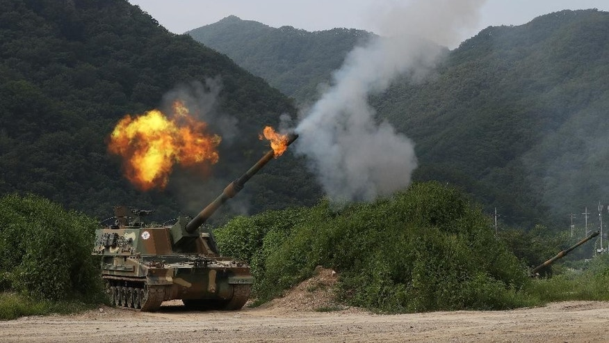 A South Korean army's K-9 self-propelled howitzer fires during a military exercise in Yeoncheon near the border with North Korea, South Korea, Thursday, Aug. 18, 2016. South Korea's army says it has conducted its largest-ever artillery drills near the tense border with North Korea. (Lim Byung-shick/Yonhap via AP). KOREA OUT