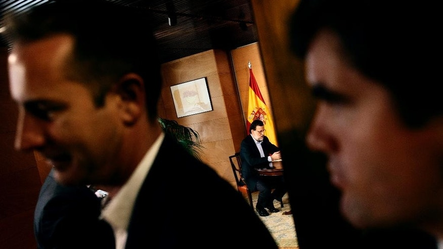 Spain's acting Prime Minister Mariano Rajoy, center background, talks with Ciudadanos party leader Albert Rivera during a meeting at the Spanish parliament in Madrid, Spain, Thursday, Aug. 18, 2016. Rajoy is meeting with the head of a minor party that says it might support his bid to form a new government, and end an eight-month political deadlock following two inconclusive elections. (AP Photo/Daniel Ochoa de Olza)
