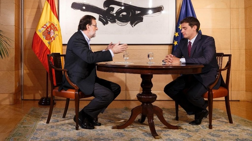 Spain's acting Prime Minister Mariano Rajoy, left, gestures as he talks with Ciudadanos party leader Albert Rivera during a meeting at the Spanish parliament in Madrid, Spain, Thursday, Aug. 18, 2016. Rajoy is meeting with the head of a minor party that says it might support his bid to form a new government, and end an eight-month political deadlock following two inconclusive elections.  (AP Photo/Daniel Ochoa de Olza)