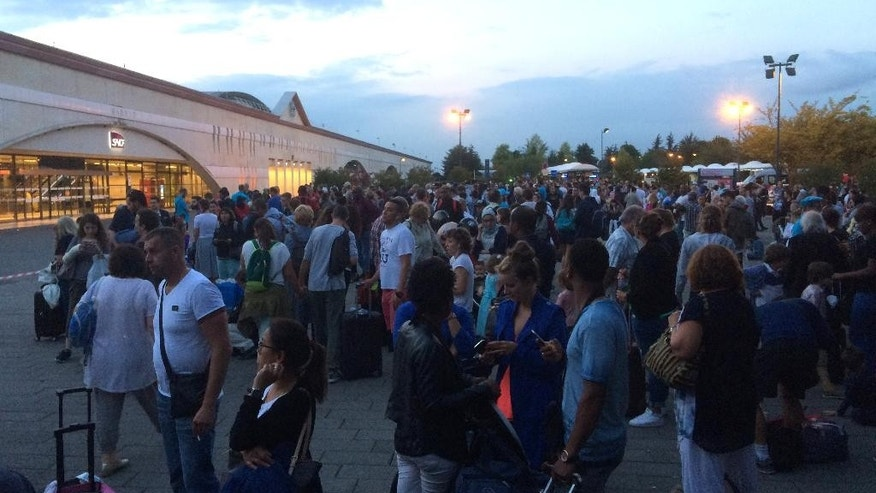 Passengers wait outside the Marne la Vallee train station, near to Disneyland east of Paris, Thursday, Aug. 18, 2016, after the station was evacuated following a warning about a suspicious package. Disneyland Paris said the park remained open to the public.  Stations close to the site have been evacuated a few times in recent weeks in false alarms amid a summer of tensions after deadly extremist attacks. (AP Photo/Philippe Sotto)