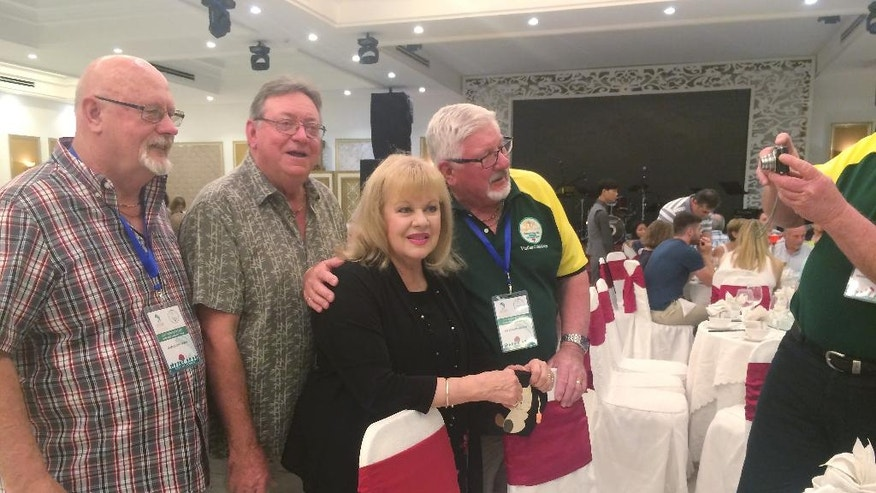 Australian singer Patricia Amphlett, better known as Little Pattie, third from left, poses for photos with fans after she was not allowed to perform by local authorities in Vung Tau, Vietnam, on Wednesday Aug. 17, 2016. Australia was making top-level appeals to Vietnam on Wednesday to lift a sudden ban on veterans commemorating the 50th anniversary of Australia's most costly battle of the Vietnam War. (AP Photo)
