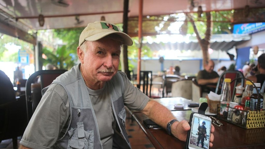 Australian veteran Jeffrey Morris shows a photo of himself taken when he served in Long Tan during the Vietnam war in Vung Tau city, Vietnam on Wednesday, 17 August 2016. Australia is making top-level appeals to Vietnam on Wednesday to lift a sudden ban on veterans commemorating the 50th anniversary of Australia's most costly battle of the Vietnam War.(AP Photo/Hau Dinh)